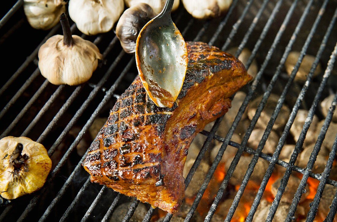 Pork and garlic cloves on a grill