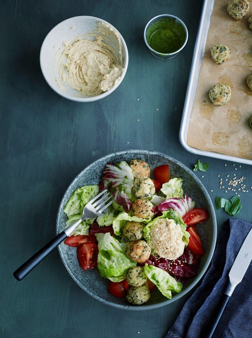 Hummus bowl with fish balls and brightly coloured salad