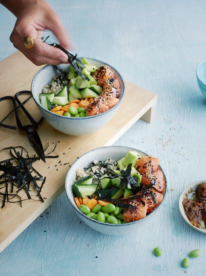 Colourful salmon sushi bowl with nori and edamame