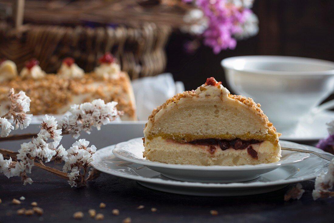 Sponge cake filled with vanilla cream, apple, mango and lingonberries, coated in hazelnut brittle (vegan)