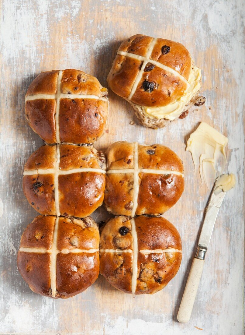Hot cross buns with butter on a wooden background (Easter baking, England)