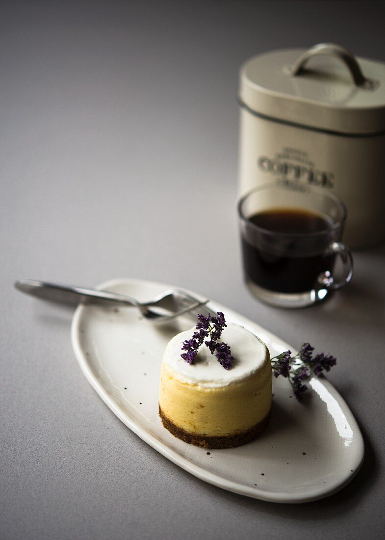 A cheesecake torte on a serving plate with a cup of coffee