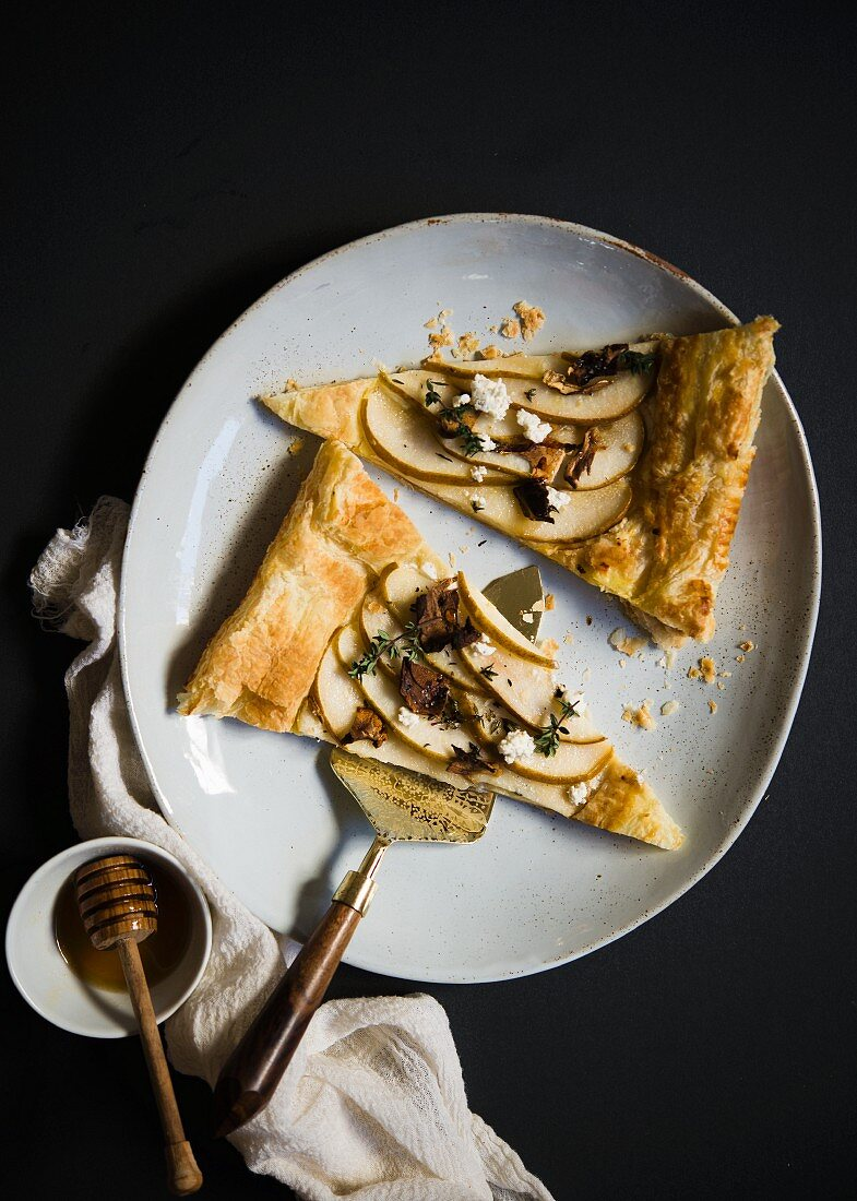 Two slices of puff pastry with pears, goat's cheese and honey (top view)