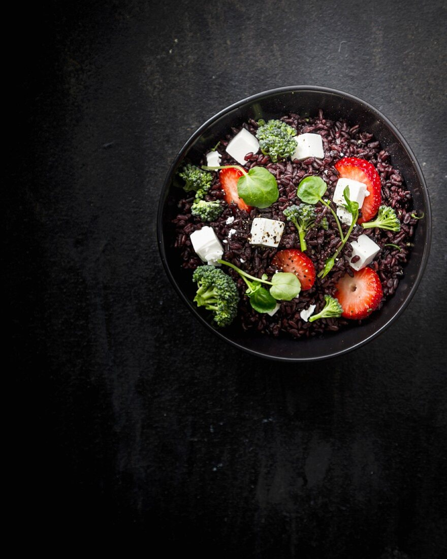 A black rice salad with strawberries, feta, broccoli and basil