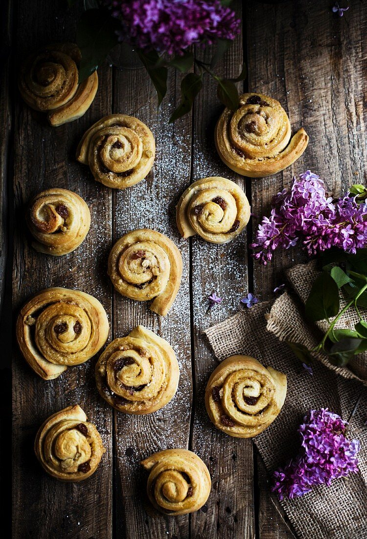 Cinnamon rolls on a wooden background, with violet lilac flowers