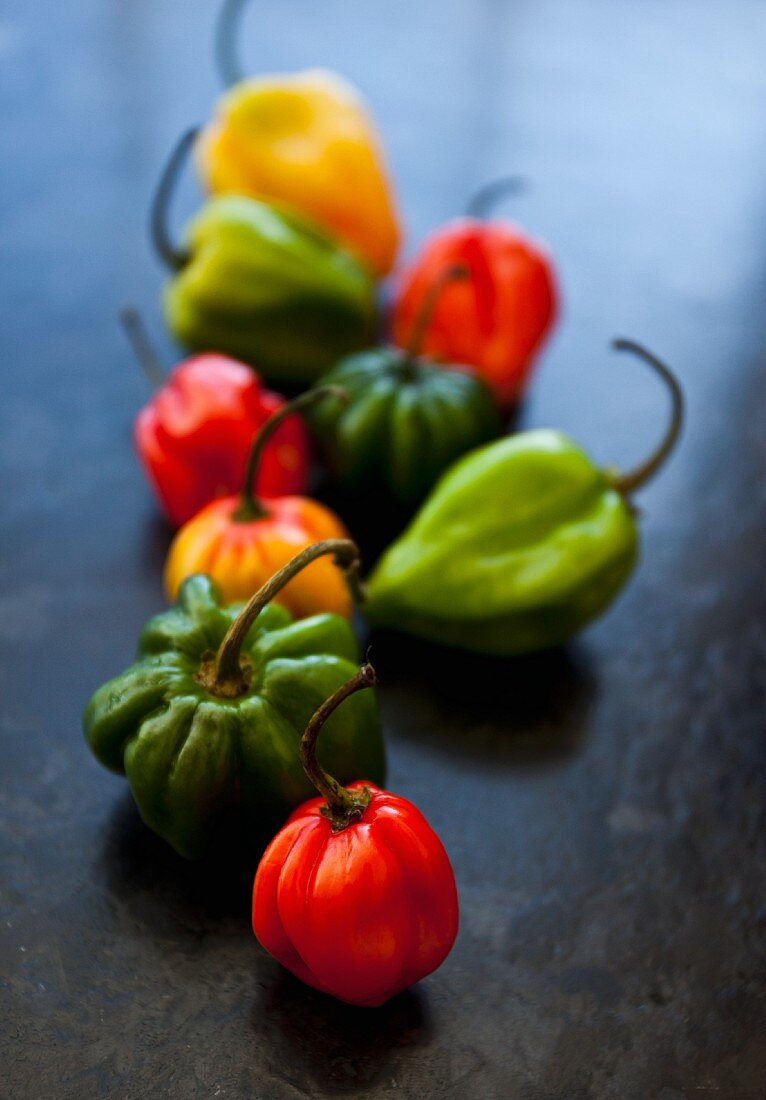 Various types of chili peppers lined up in a row on a black slate countertop