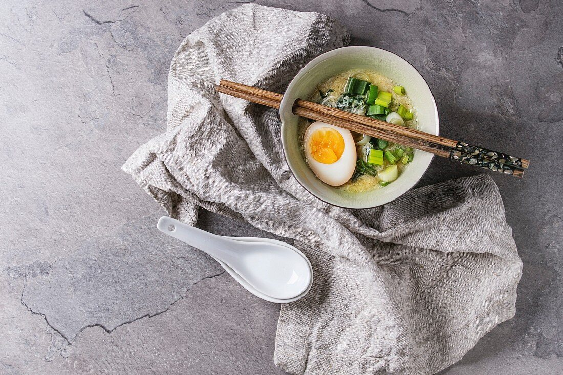 White bowl of asian style soup with scrambled eggs, half of marinated egg, spring onion, spinach