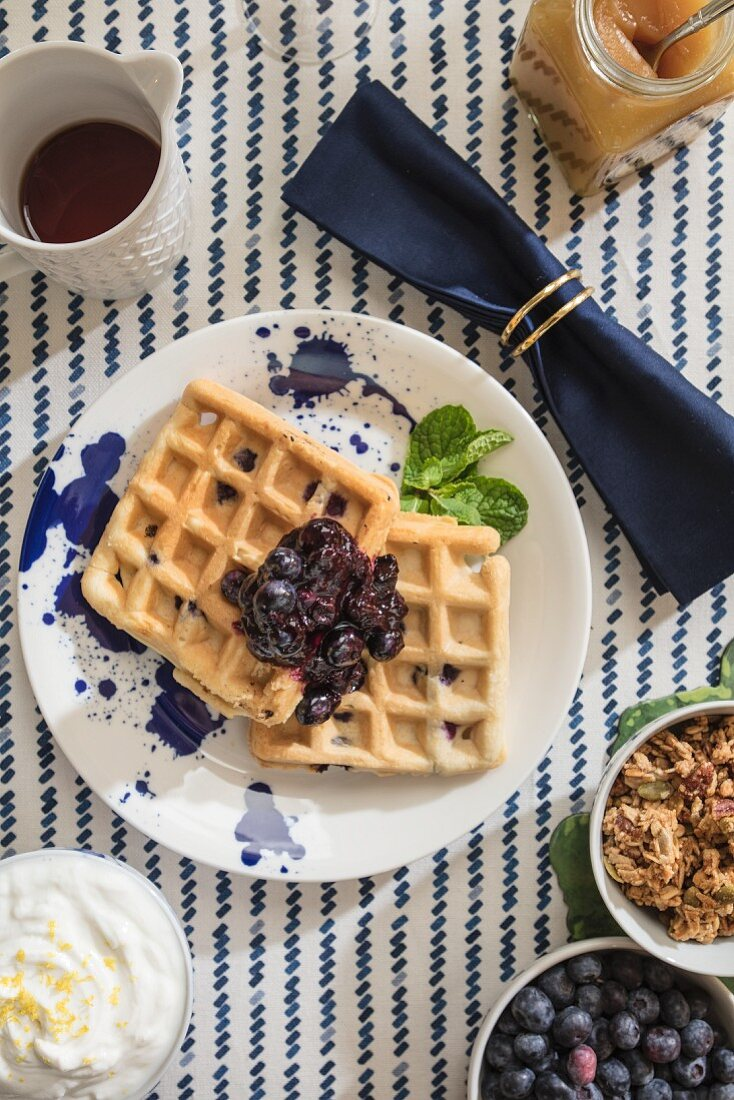 Blueberry Lemon Waffles shot from overhead on table styled with sptriped tablecloth and navy rolled napkin