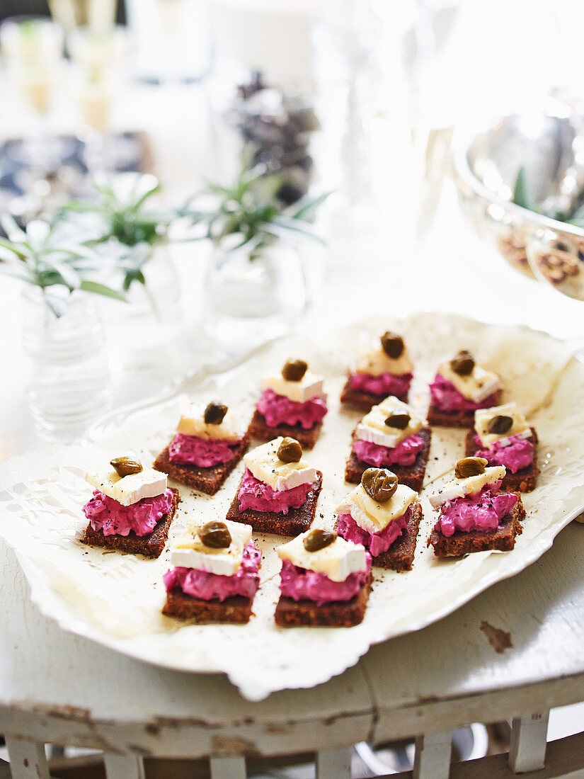 Pumpernickel bread topped with beetroot and soft cheese for New Year's Eve