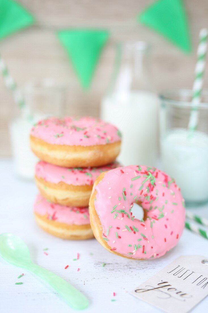 Pink doughnuts and glasses of milk