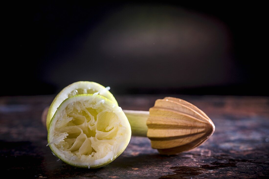 A squeezed lemon next to a wooden citrus reamer