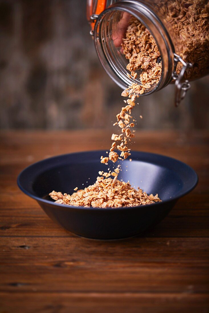 Muesli being poured out of a storage jar into a small bowl