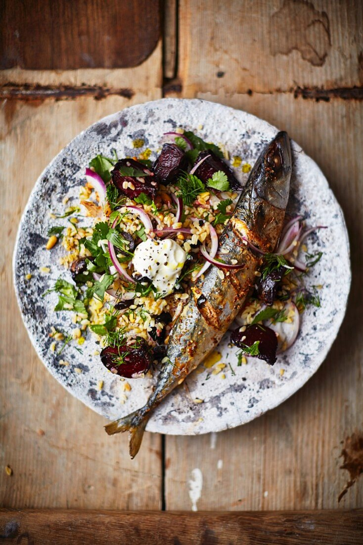 Roasted mackerel on bulgur with beetroot and onion (seen from above)