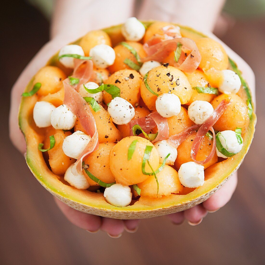Melon salad with mozzarella and proscuitto in a hollowed-out melon