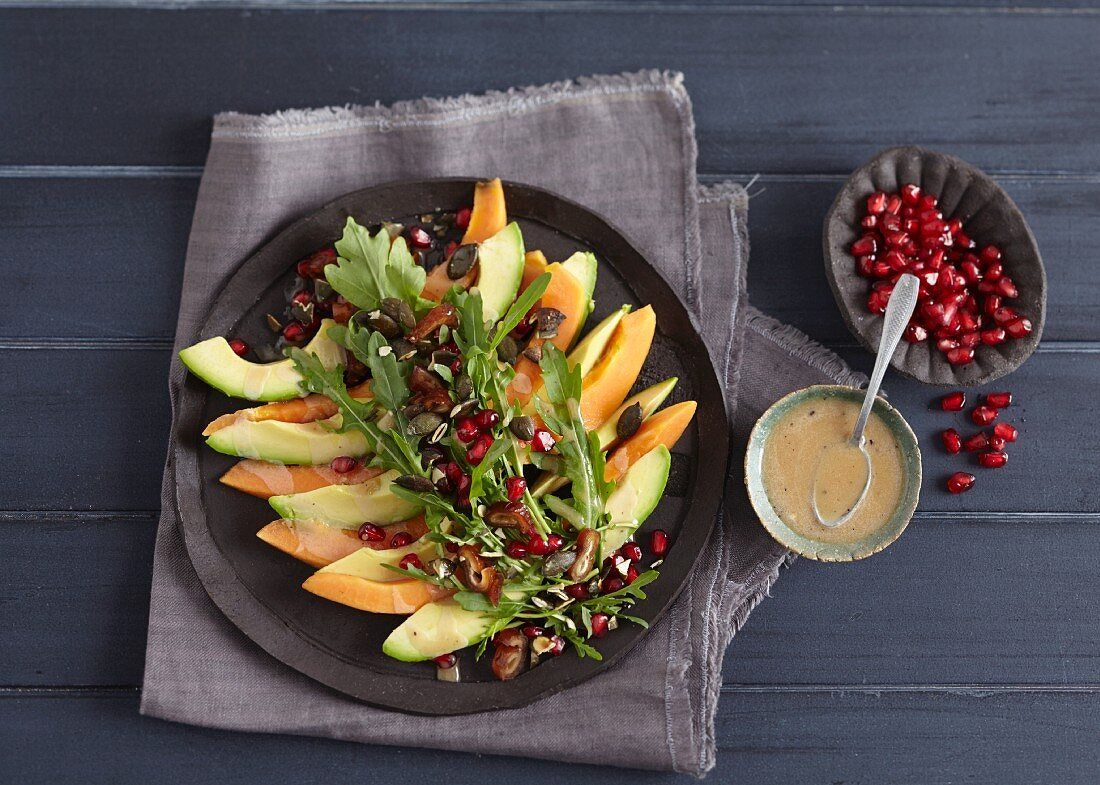 A superfood salad with avocado, papaya and pomegranate seeds