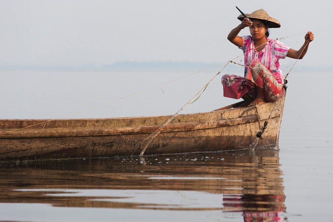 A young Asian woman fishing at Indawgyi Lake (Kachin, Myanmar, Burma)