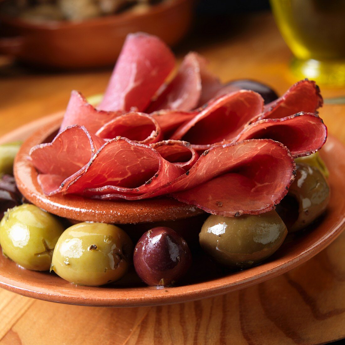 Bresaola, Italian air dried beef with olives as appetizer