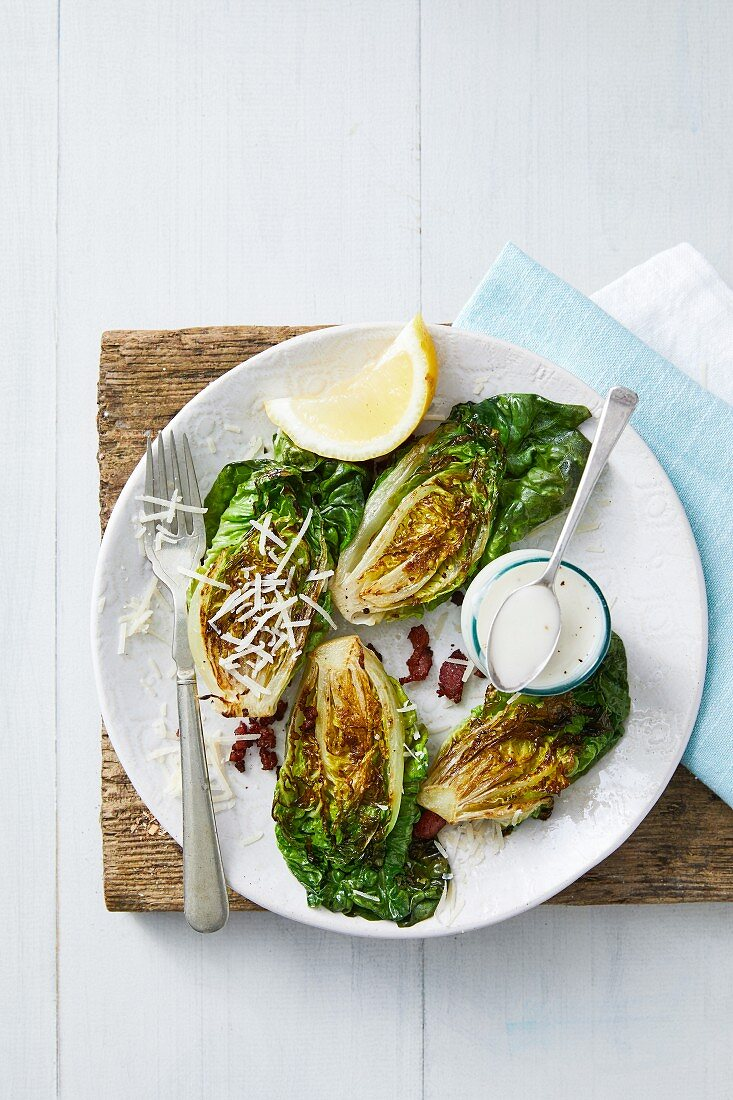 Grilled romaine lettuce with bacon, parmesan and a Caesar dressing