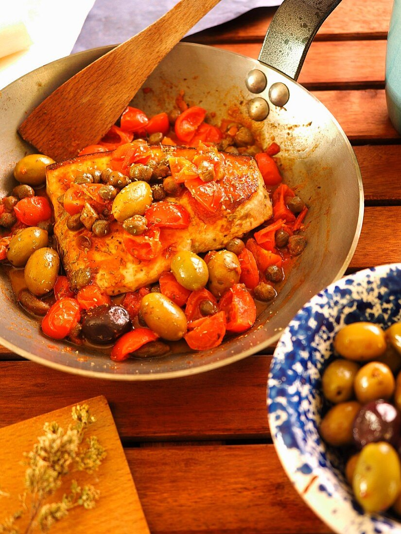 Pesce Spada alla Ghiotta, traditional swordfish calabrian recipe with capers, olives, tomato, red onions and oregano, Calabria, Italy, Europe