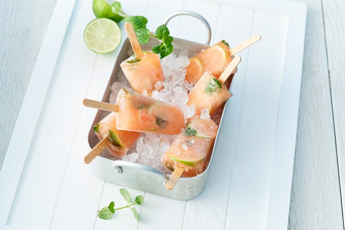 Lime and papaya ice lollies with mint on crushed ice in a metal tray