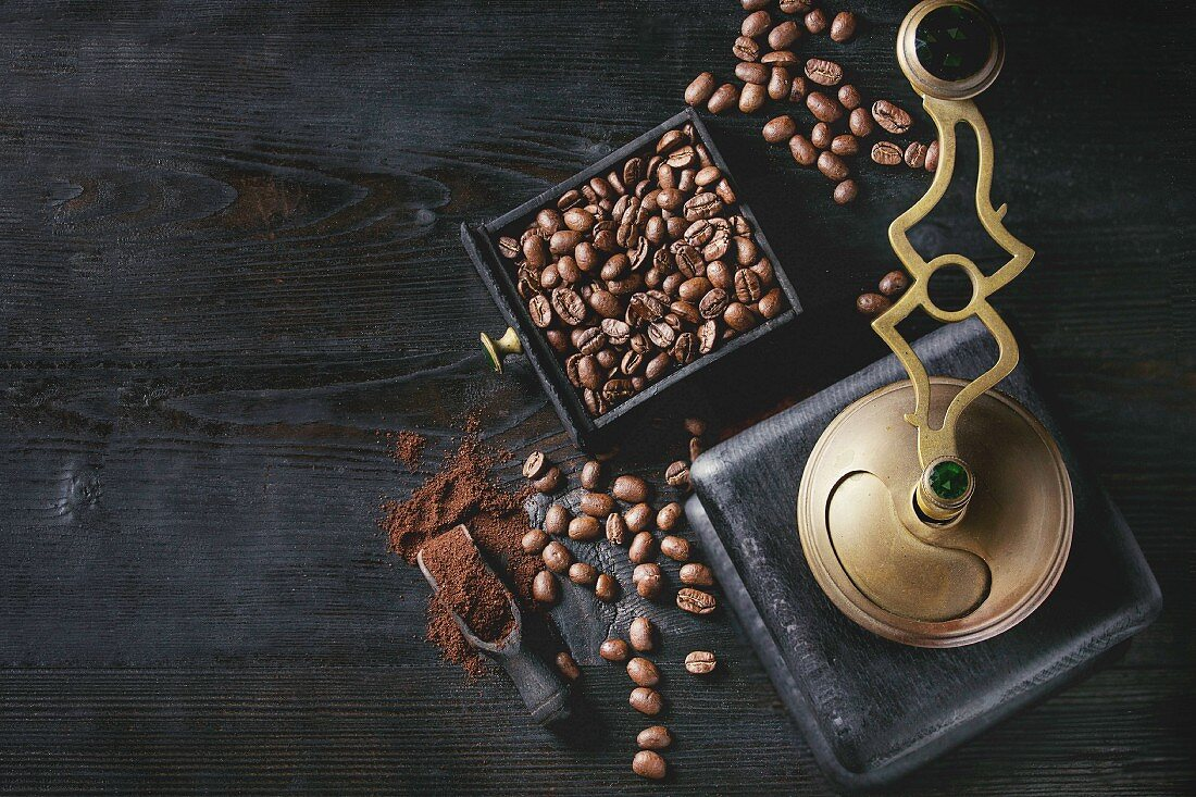Roasted coffee beans and grind coffee in wood box with vintage coffee grinder and scoop over black wooden burnt background