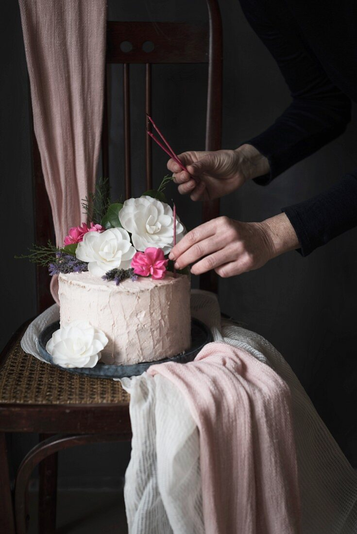 An iced birthday cake decorated with flowers, on a chair, with candles.