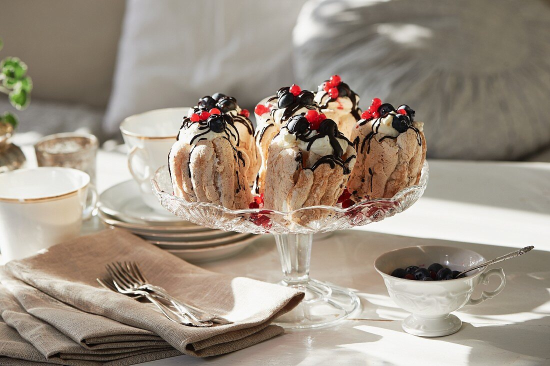A meringue dessert with cream, berries and chocolate sauce