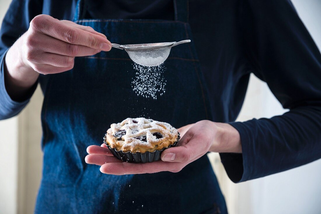 A woman dusting vegan blueberry tarts with icing sugar