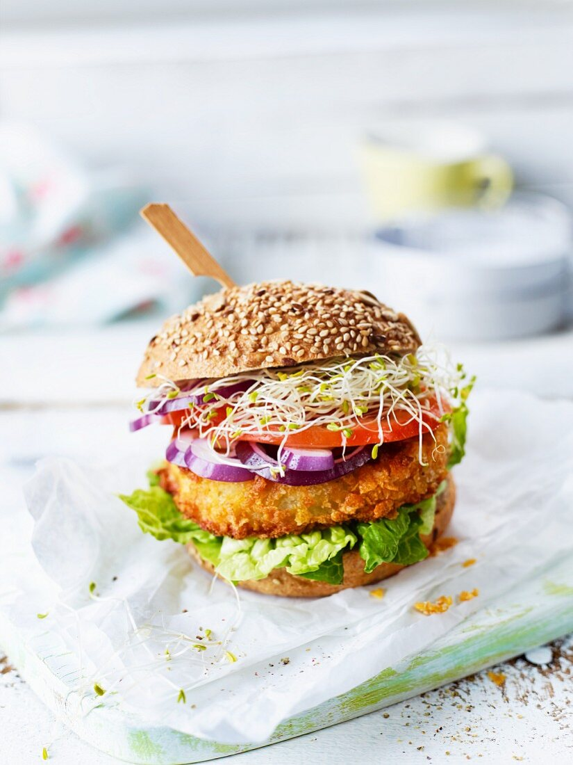 A veggie burger with sliced cabbage, lettuce, tomato and sprouts