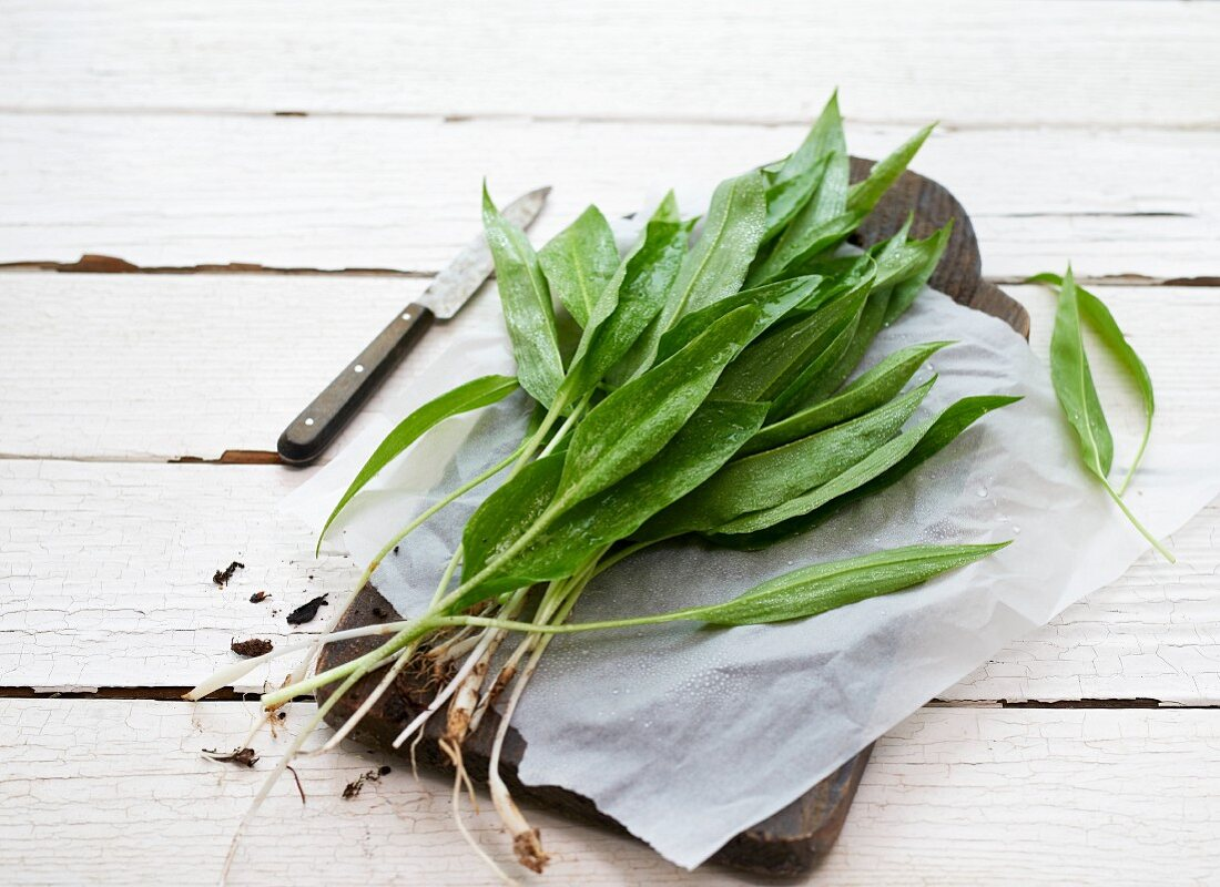 Fresh wild garlic on paper and a wooden chopping board