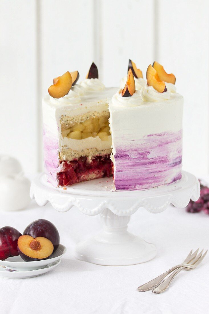A plum, apple, and poppy cake with whipped cream