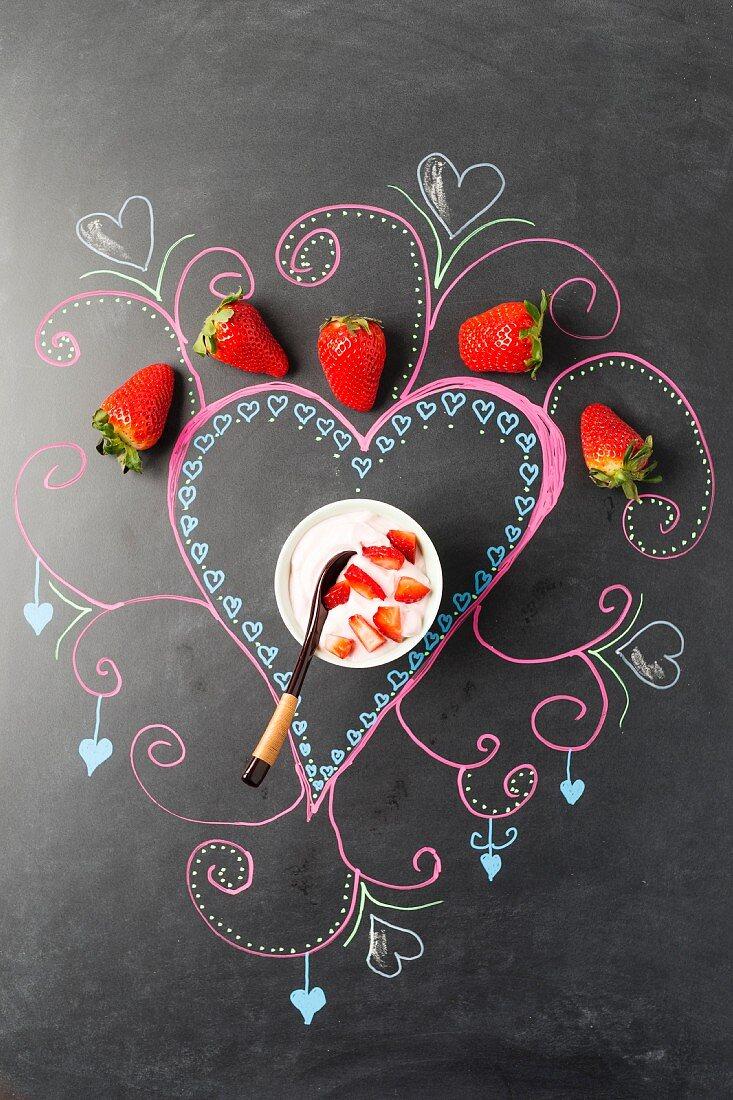 A strawberry dessert on a decorated blackboard