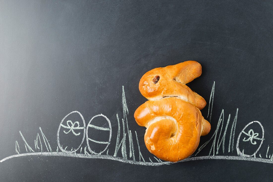 A yeast dough Easter bunny on a decorated blackboard