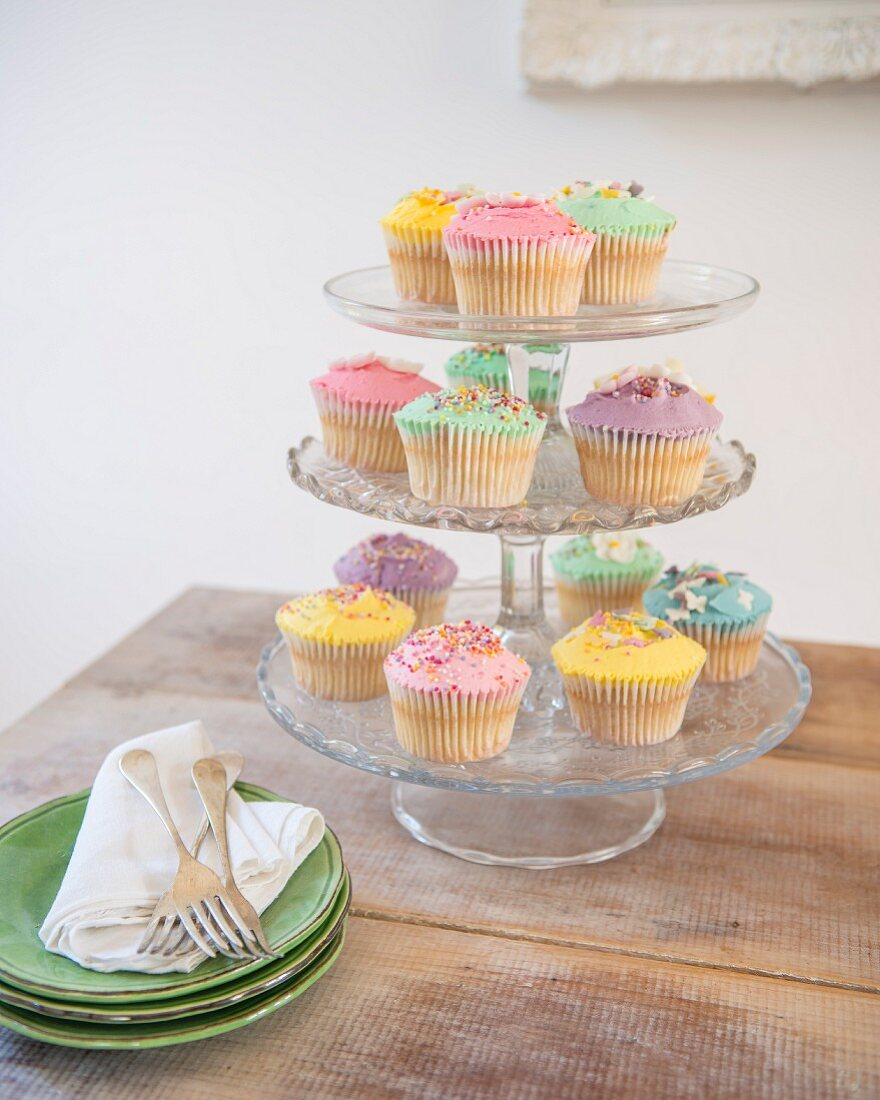 Pastel cupcakes decorated with colourful hundreds-and-thousands next to stacked plates on rustic table