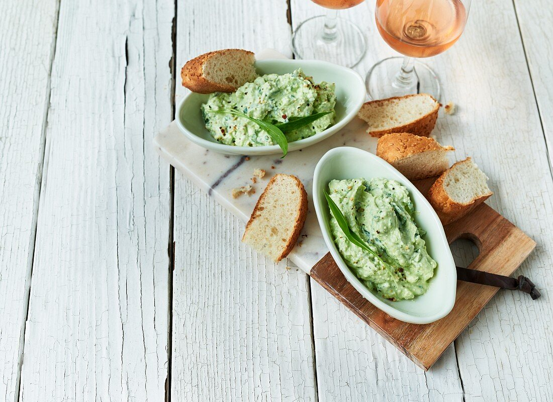 Bear's garlic dip with sheep's cheese, sesame bread slices, and wine