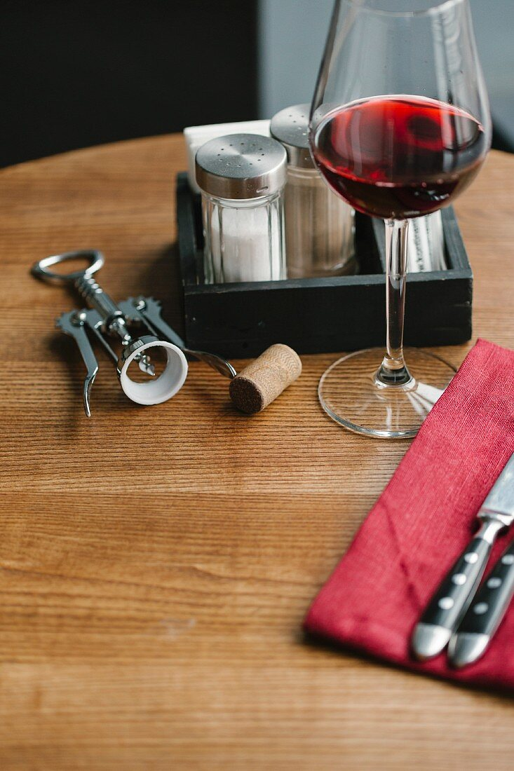A glass of red wine, a corkscrew, cutlery, and salt and pepper shakers on a table