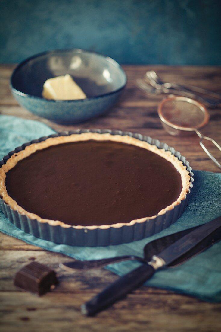 A whole chocolate tart in a baking tin
