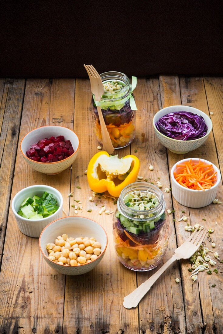 Two glasses of rainbow salad with chick-peas, sprouts and different vegetables and bowls with ingredients