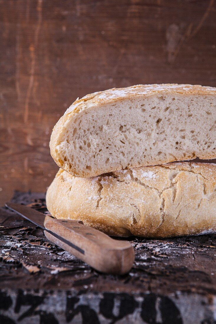 Wheat bread baked in a tin: A halved loaf with a knife on a wooden table