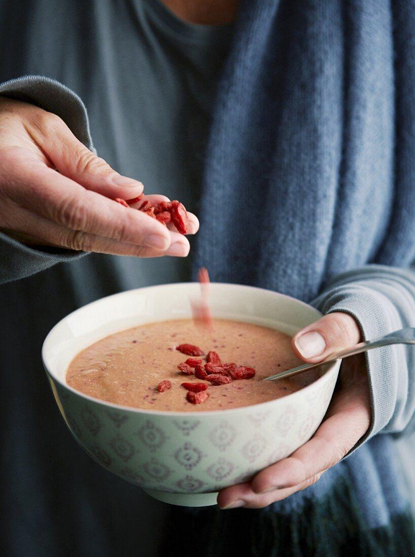 Vegan plum and amaranth porridge with goji berries
