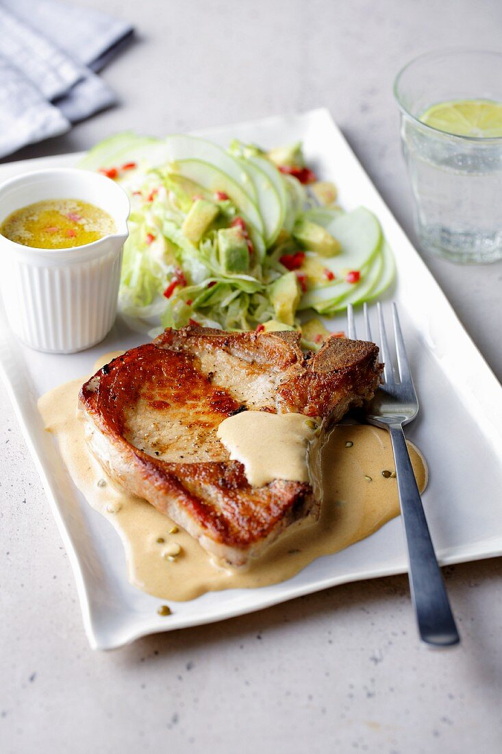 Fried pork chop with spicy apple and avocado salad
