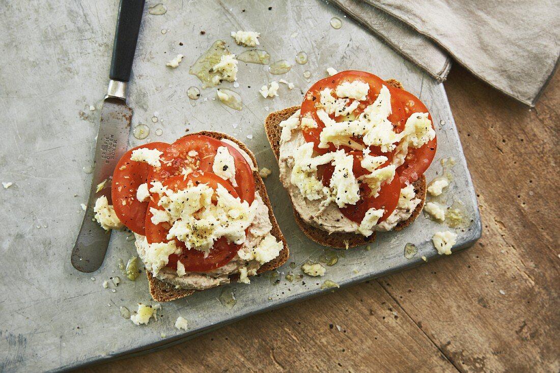 An open sandwich on spelt bread with tuna and cinnamon cream, tomatoes and mozzarella