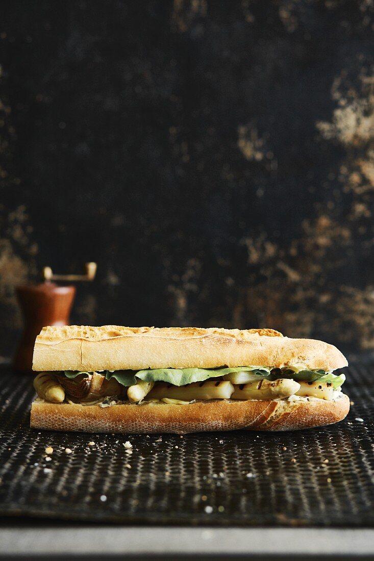 A baguette sandwich with white asparagus, artichokes and lavender butter