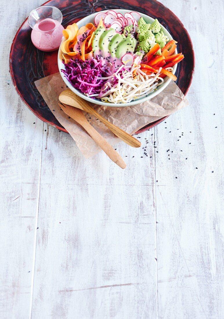 A raw Buddha bowl with raspberry dressing