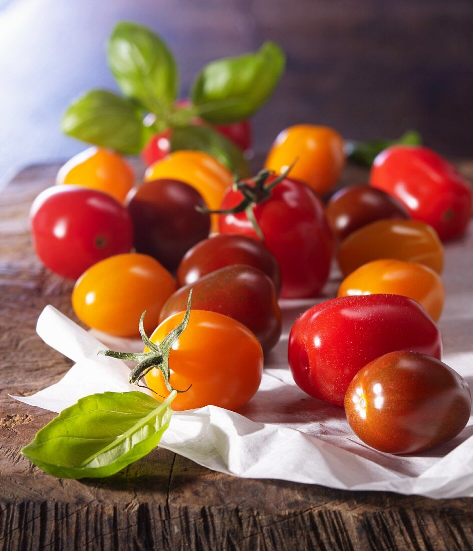 Different types of mini tomato with basil on paper and a wooden board