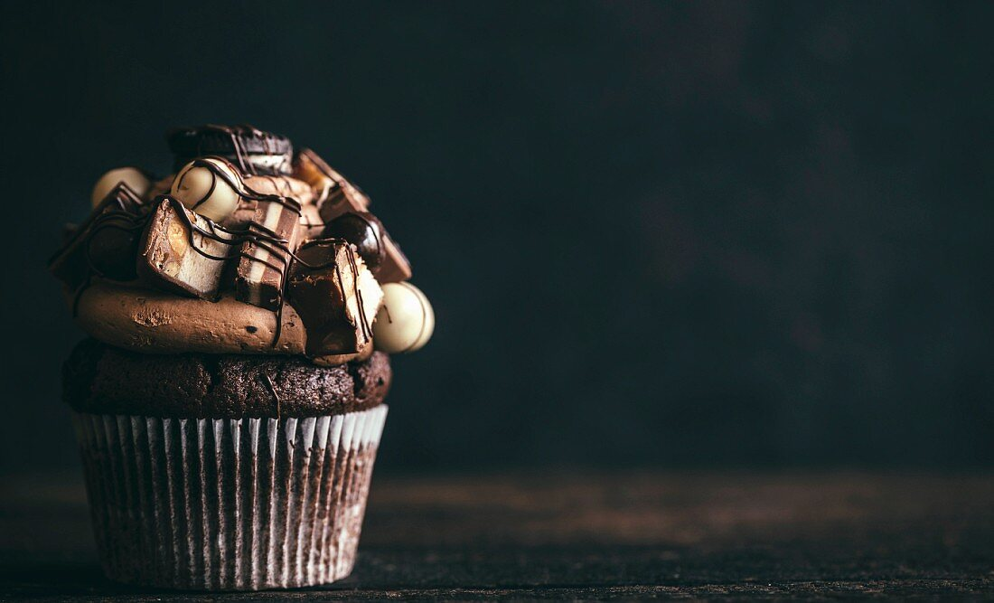A chocolate cupcake with sweets on the top for a party