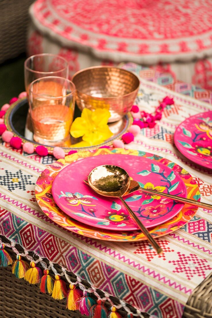 Table brightly set with ethnic patterns and copper