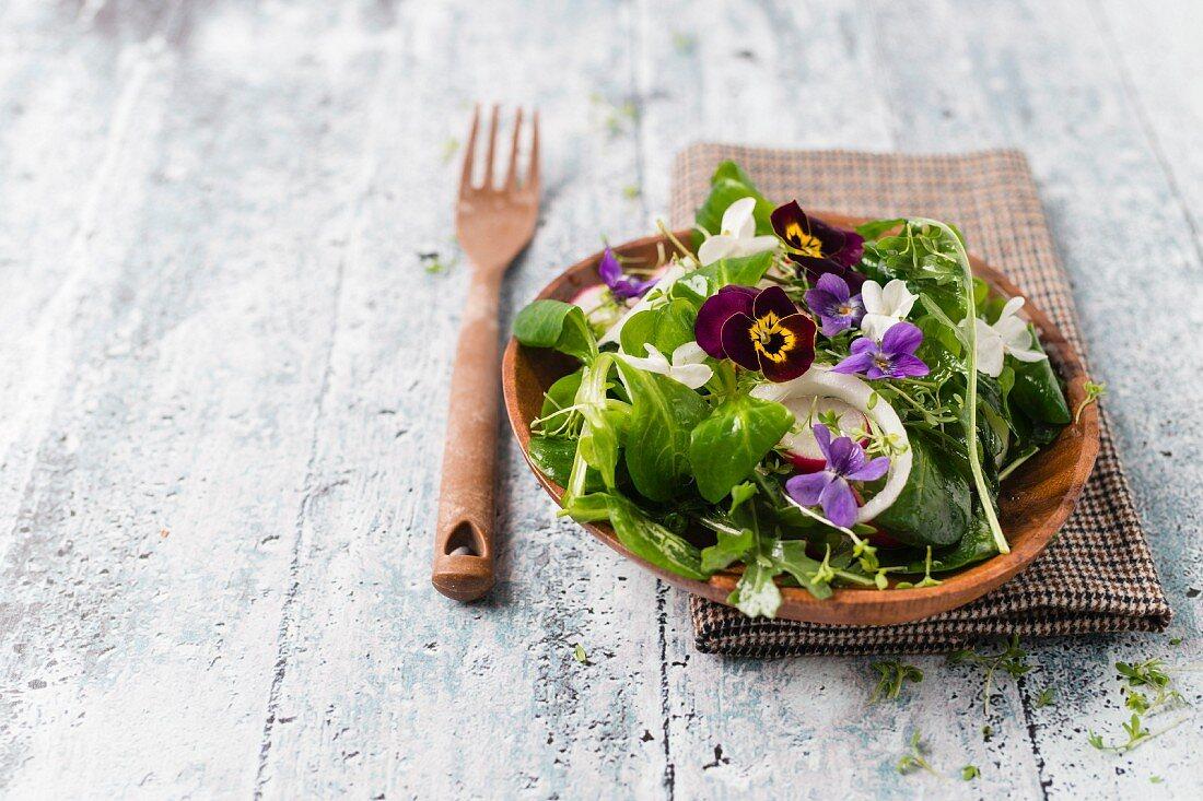 Frühlingssalat mit Rucola, Feldsalat, Radieschen, Zwiebelringen, Kresse und Essblüten