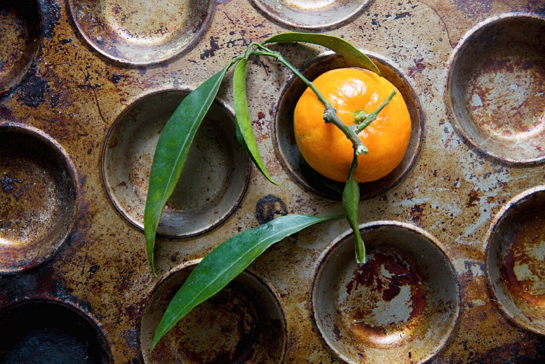 A clementine with leaves in a baking tin