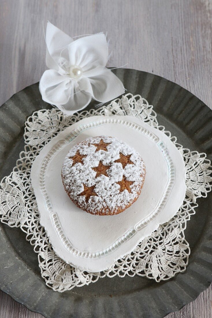Homemade gingerbread with icing sugar dusted in a star pattern, on a lace doily (gluten-free)